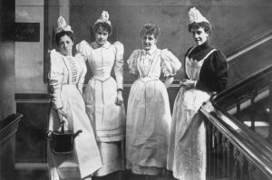 1892- Maids pausing on the stairs at the London hotel where they work